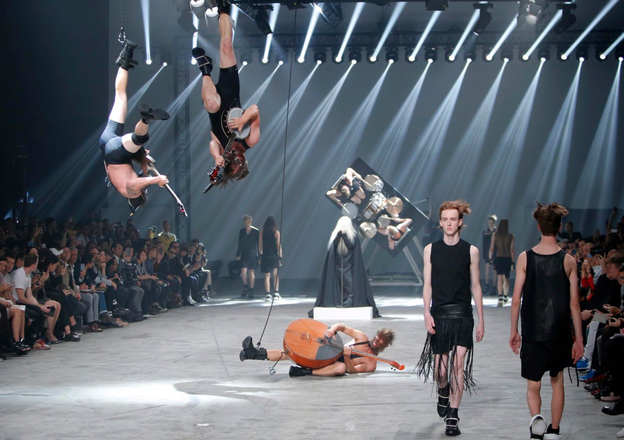 Winny Puhh ...Models wear creations by fashion designer Rick Owens as part of his men's fashion Spring-Summer 2014 collection, presented Thursday, June 27, 2013 in Paris, as Estonian metal/punk band Winny Puhh perform live, suspended by their feet . (AP Photo/Francois Mori)